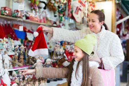 niños de compras: Madre alegre con la pequeña hija de la compra de regalos de Navidad en el mercado. Centrarse en la niña