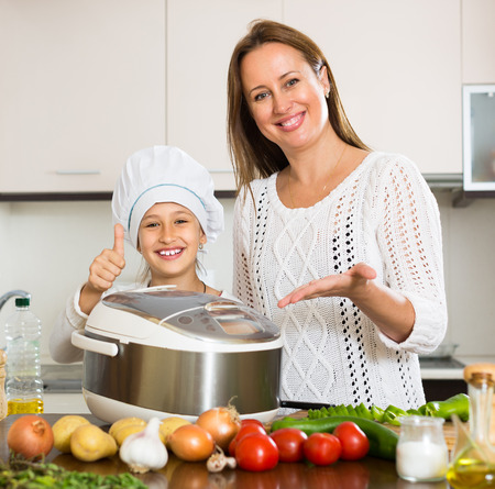 slow cooker: Slow cooker helping mother and smiling daughter to prepare dinner at home kitchen Stock Photo