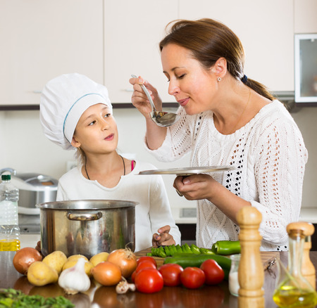 mom: Portrait of cheerful daughter and mom with vegetables and casserole in kitchen at home. Focus on girl