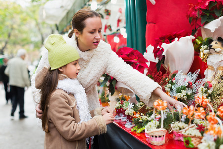 adornment: Young  woman with little daughter looking at adornment with conifer in Christmas market. Focus on girl