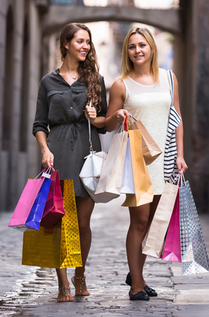 gladful: Two cheerful female friends with shopping bags in hands walking by street Stock Photo