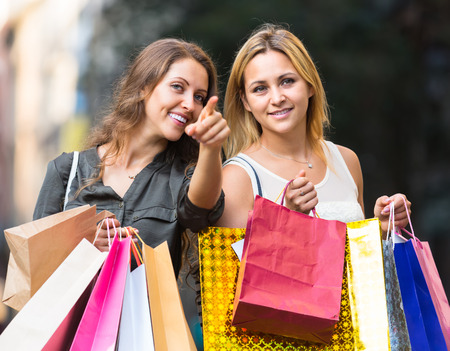 gladful: Portrait of two beautiful smiling girls with shopping bags at street