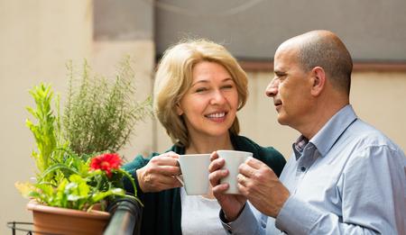 tercera edad: Sonriente pareja madura mayores que charlan en el balcón con las tazas de té en las manos
