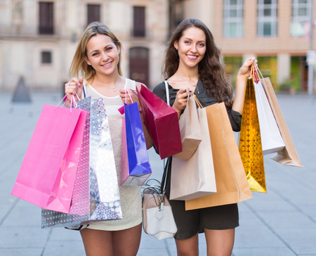 spendthrift: friends carrying bags with purchases outdoors