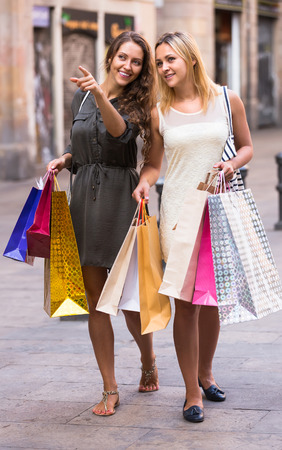 spendthrift: Two smiling female friends with shopping bags at street Stock Photo