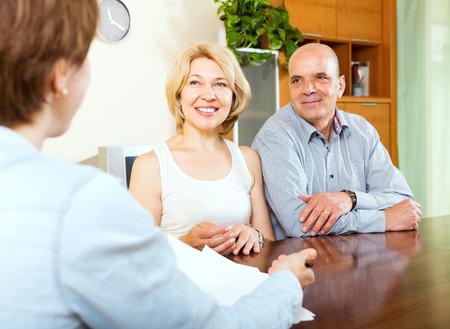 empleada domestica: Pareja mayor escuchando gerente mujer con papeles Foto de archivo