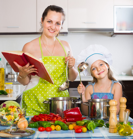 spanish woman: Smiling spanish woman and daughter preparing food consulting the cookbook Stock Photo