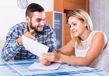 middle joint: Smiling couple at the table  filling forms for joint banking account