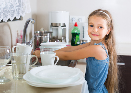 glimlachend Europees vrouwelijk kind die dishware thuis schoonmaken