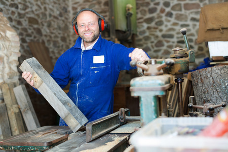 workroom: Happy professional woodworker on lathe at musical instrument workroom