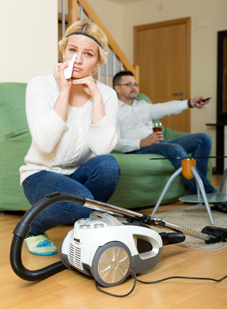 tidying up: Crying woman tidying up, husband relaxing on couch Stock Photo