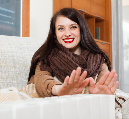 Portrait of happy girl in scarf  warming near warm heater  in home Stock Photo