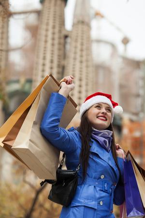ropa de invierno: Mujer con las compras en contra de la Sagrada Familia durante las ventas de Navidad en Barcelona,