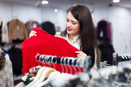 'pull over': Ordinary woman choosing sweater at clothing store