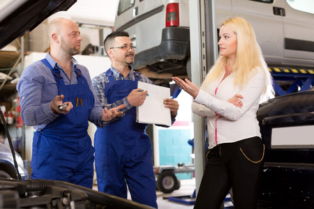specialists: Unhappy young girl talking with specialists at auto repair shop. Focus on the left man and woman Stock Photo