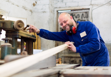 sawyer: Happy smiling atelier dressed in a blue workwear building a wooden detail from a plank of wood on a wood-working machine