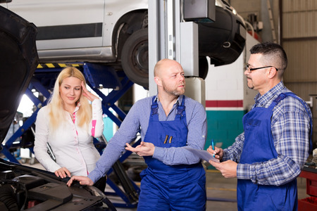 specialists: worried young woman and specialists at auto repair shop. Focus on the men Stock Photo