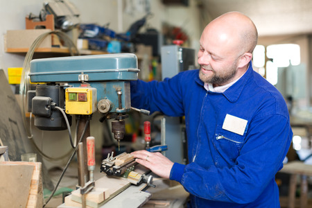 toolroom: Professional carpenter using a boring mill to drill a hole in a piece of wood Stock Photo