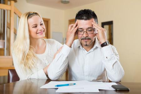 reassuring: Depressed husband calculating invoices, wife reassuring him