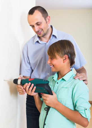 modifying: Happy man and son using electric drill at home