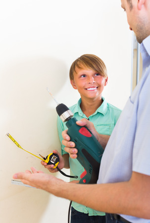 modifying: happy teenager assist father to using electric drill wall at home