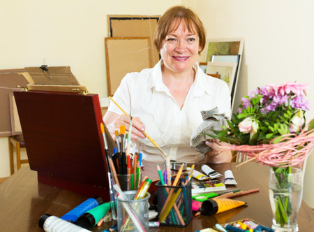 contentedness: Happy mature woman painting a new picture