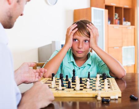 ajedrez: Padre e hijo jugando al ajedrez en casa, muchacho perder