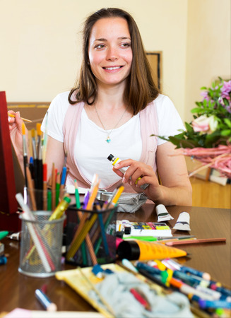 contentedness: Portrait a cheerful young artist paints a picture at home