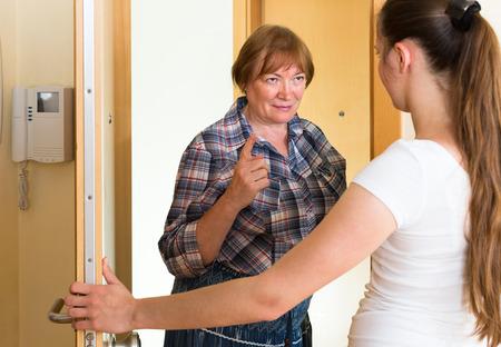 Two unpleased women standing at doorway