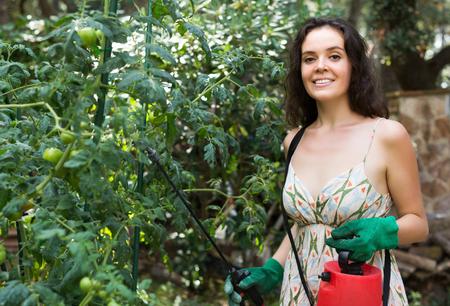 knapsack: Smiling girl working in garden with knapsack garden spray Stock Photo