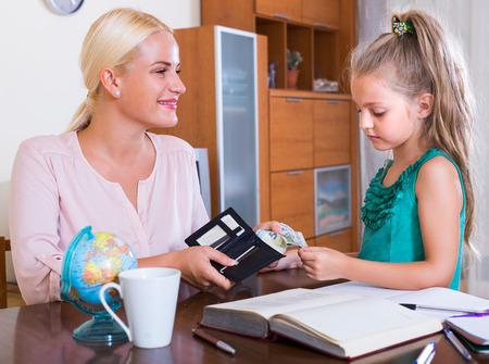 Toelage van zakgeld: meisje en glimlachende moeder met beurs Stockfoto