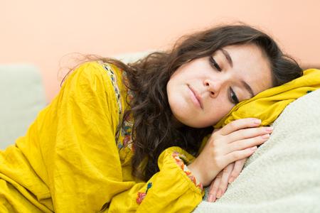 femme triste: femme triste et solitaire couch� sur un canap� � la maison