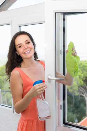 atomizer: Happy woman cleaning windows using atomizer indoor