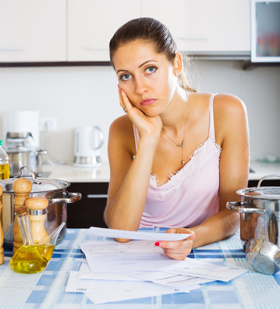 dispirited: Tired and upset housewife reading bills at the kitchen