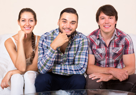 bisexual: Polyandry: a happy woman and two men smiling indoors Stock Photo