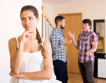 polygamy: Quarrel among adult couple at home in the living room Stock Photo