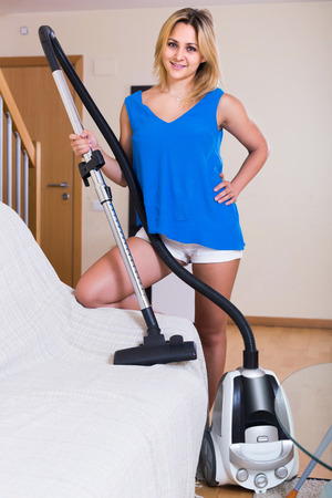 indoors: Young european maid using modern hoover during clean-up indoors Stock Photo