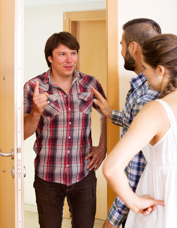 complaining: Sad neighbor standing at entrance and complaining about noise. Focus on the man Stock Photo