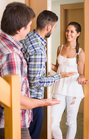 ordinary woman: family couple inviting friend in the apartment