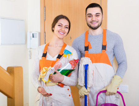 houseman: Portrait of professional cleaners with equipment standing at doors of client house