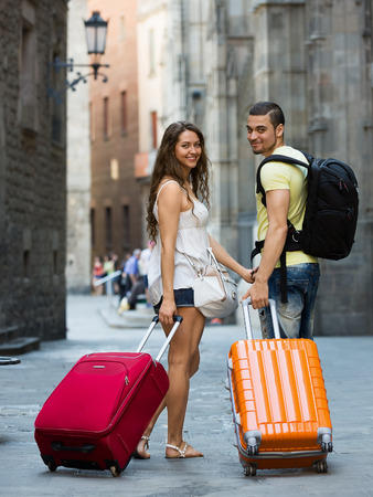 rucksack ': Smiling couple in shorts with luggage walking through city street