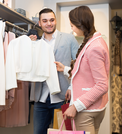 look for: Handsome husband helping happy wife to look for new clothes
