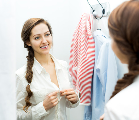 brune: Cheerful young girl with new garment at fitting-room Stock Photo