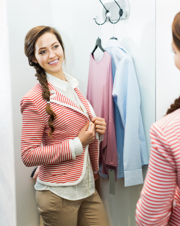 brune: Attractive girl trying on new blouse at apparel store