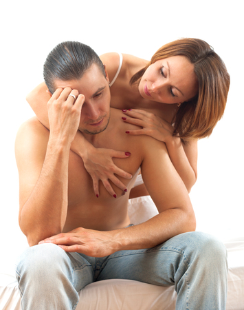 nude wife: Sad man with a problem in bed, woman consoling him in bedroom at home Stock Photo