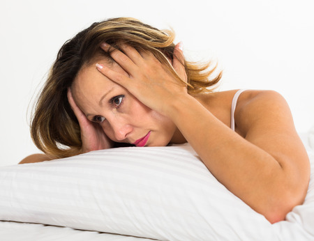 ennui: Upset long-haired woman laying in bed with dropped eyes