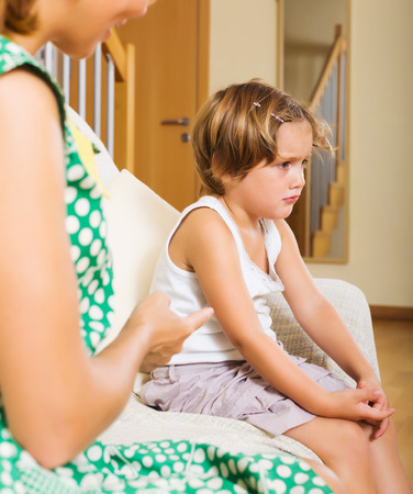 berate: Woman scolding crying little daughter at sofa Stock Photo