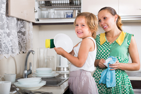 mother helping baby: Smiling baby girl helping mother washing dishes in the kitchen. Focus on girl