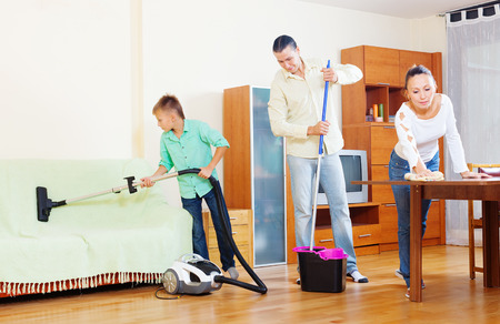 ordinary: Ordinary family doing house cleaning with  cleaning equipment in living room Stock Photo