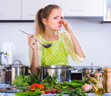 25s: Worried young housewife smelling stale soup indoors Stock Photo